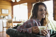 Smiling young woman drinking coffee on cabin sofa - HEROF25970
