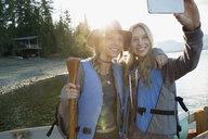 Smiling young women taking selfie life jackets lakeside - HEROF25982
