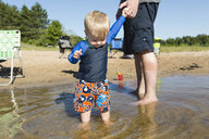 Low section of father holding cute son's hand while standing in lake against clear sky - CAVF60791
