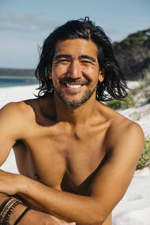 Portrait of happy shirtless man sitting at Hyams Beach against sky during sunny day - CAVF60800