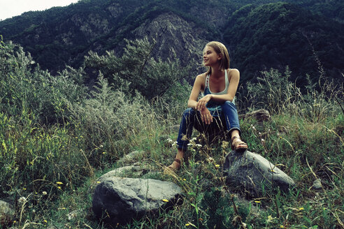 Low angle view of woman looking away while sitting on grassy field against mountain - CAVF60806