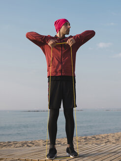 Full length of man pulling resistance band while exercising at beach against sky - CAVF60821