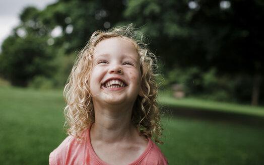 Cute cheerful girl looking away at park - CAVF60848