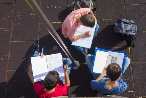 High angle view of friends studying while sitting on footpath during sunny day - CAVF60860