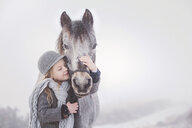 Cute girl embracing pony against sky during winter - CAVF60884