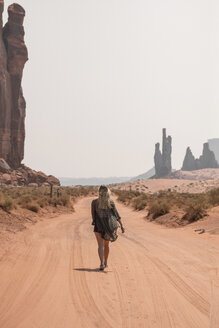 Rear view of female hiker walking on sand against sky in Monument Valley Tribal Park during sunny day - CAVF60917