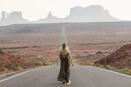 Rear view of woman walking on road against clear sky in Monument Valley Tribal Park - CAVF60920