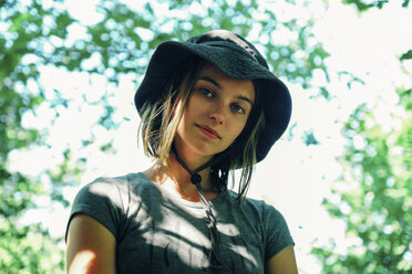 Low angle portrait of woman wearing hat while standing against trees - CAVF60941