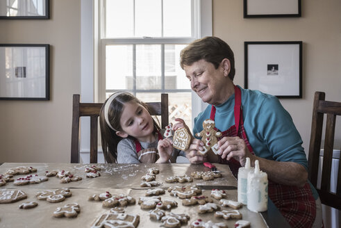 Cute granddaughter showing gingerbread cookies to grandmother at home - CAVF60968