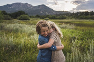 Happy sisters embracing while standing on grassy field in forest during sunset - CAVF61007