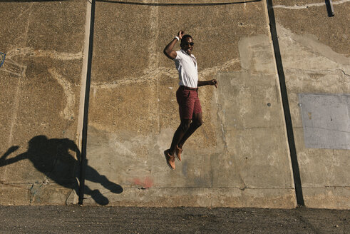 Happy male dancer wearing sunglasses while jumping against old wall during sunny day - CAVF61010