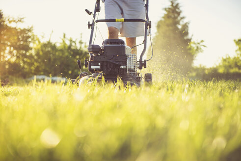 Midsection of man mowing grassy field against sky in yard during sunset - CAVF61025