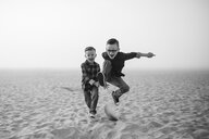 Playful brothers jumping on sand at beach against sky during foggy weather - CAVF61040