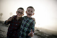 Portrait of cute happy brothers standing at beach against sky during foggy weather - CAVF61046