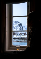 Pensive woman looking out window at snowy mountain, Reine, Lofoten Islands, Norway - CAIF22620