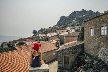 Woman in red hat looking at buildings on hillside, Monsanto, Portugal - CAIF22632