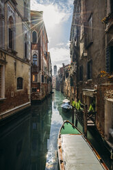 Sun shining over tranquil buildings and canal with gondolas, Venice, Italy - CAIF22635