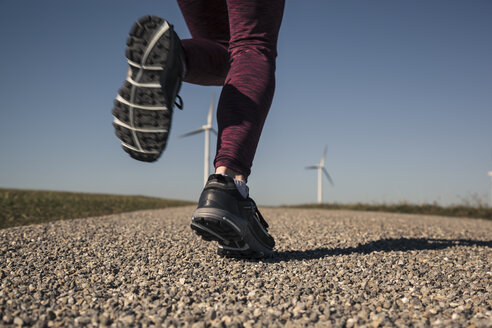 Young woman jogging on field way, wind wheels in the background - SEBF00002