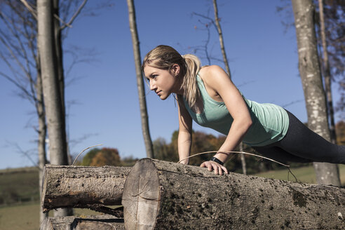Young woman doing pushups on tree trunk during workout in nature - SEBF00008