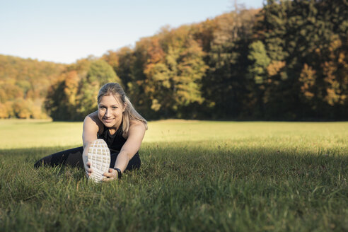 Young woman stretching her leg on a meadow - SEBF00014