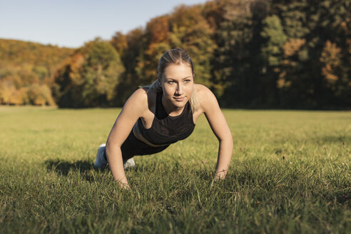 Young woman doing pushups during workout on meadow - SEBF00017