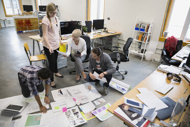 Graphic designers meeting reviewing proofs on office floor - HEROF26096