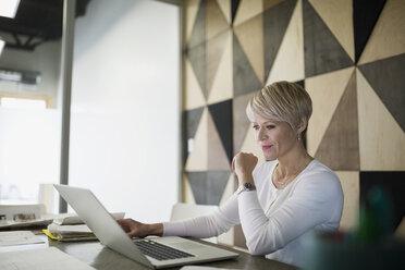 Focused businesswoman working at laptop in conference room - HEROF26099
