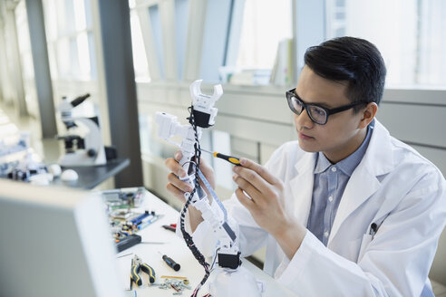 Focused engineer in lab coat assembling robotic arm - HEROF26120