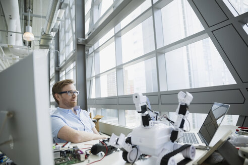 Pensive engineer at desk with robot - HEROF26123
