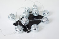 Close-up of mirror ball fairy lights on tablet - MOEF02073