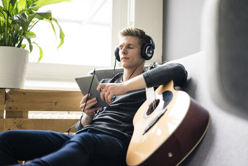 Relaxed young man with tablet and guitar listening to music with headphones - MOEF02082