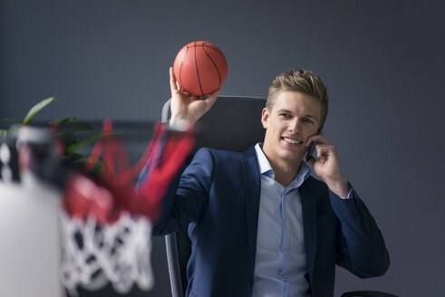 Young businessman sitting at desk in office playing basketball and talking on cell phone - MOEF02085