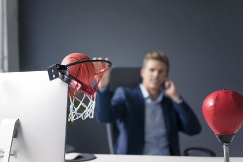 Young businessman sitting at desk in office playing basketball and talking on cell phone - MOEF02088