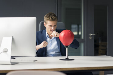 Young businessman at desk in office boxing with punching ball - MOEF02094