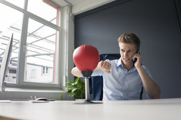 Young businessman at desk in office boxing with punching ball and talking on cell phone - MOEF02100