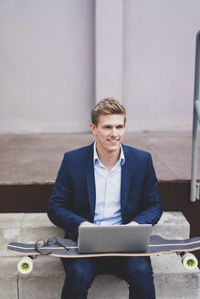 Smiling young businessman with skateboard sitting outdoors on stairs using laptop - MOEF02118