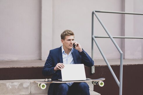 Young businessman with skateboard and laptop sitting outdoors on stairs talking on cell phone - MOEF02121