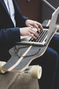 Close-up of young businessman with skateboard using laptop - MOEF02127