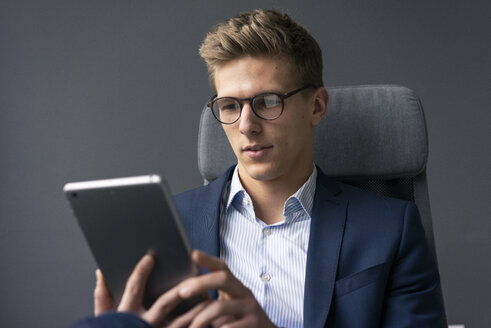 Young businessman sitting on office chair using tablet - MOEF02133