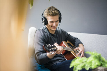 Smiling young man with headphones sitting on couch playing guitar - MOEF02142