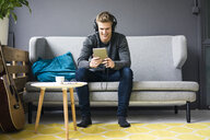 Smiling young man with guitar, tablet and headphones sitting on couch - MOEF02145