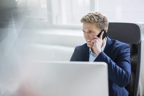 Smiling young businessman sitting at desk in office talking on cell phone - MOEF02160