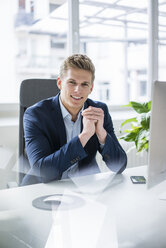 Portrait of confident young businessman sitting at desk in office - MOEF02163