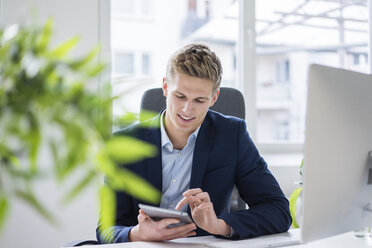 Confident young businessman sitting at desk in office using tablet - MOEF02166