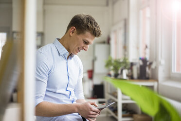 Smiling young businessman using tablet in office - MOEF02169