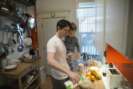 Father and son in pajamas preparing cereal kitchen - HEROF26164