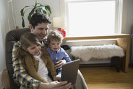 Father and children using digital tablet living room - HEROF26167