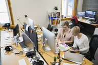 Businesswomen reviewing paperwork at desk in office - HEROF26203