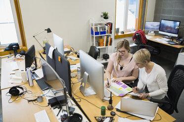 Businesswomen reviewing paperwork at desk in office - HEROF26203