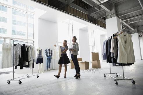 Fashion stylists examining blouse in studio - HEROF26260